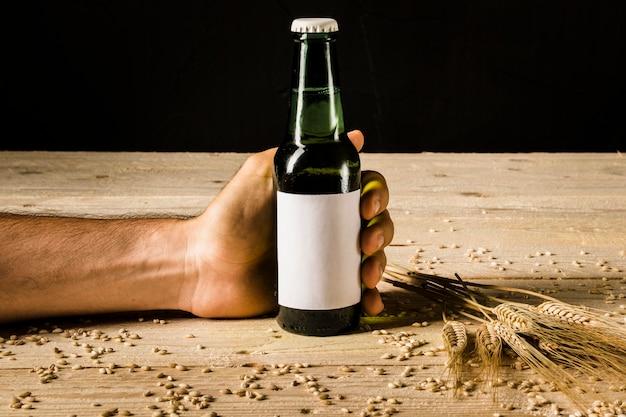 Main de l'homme tenant une bouteille de bière avec des épis de blé sur une surface en bois Photo gratuit