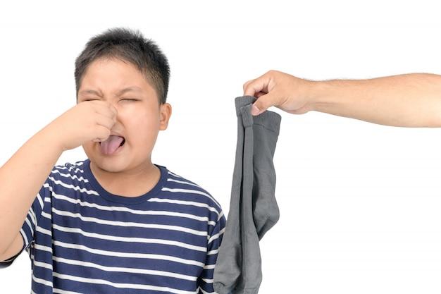 Main de l'homme tenant des chaussettes puantes sales isolées Photo Premium