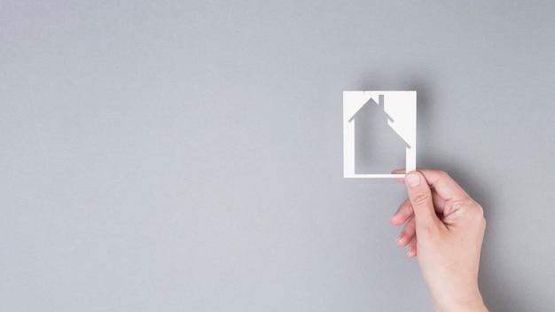 Main de l'homme tenant la découpe de la maison sur fond gris Photo gratuit