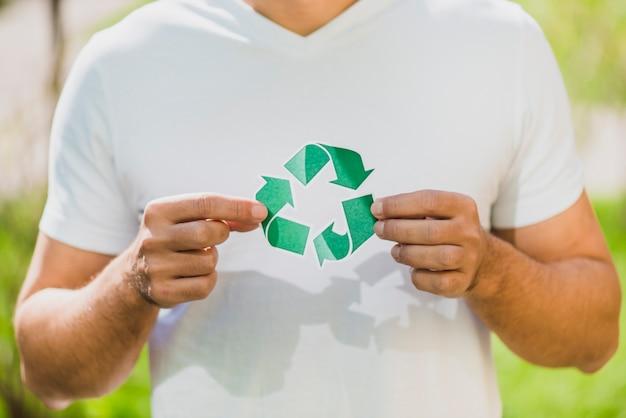 Une main d'homme tenant une icône de recyclage Photo gratuit