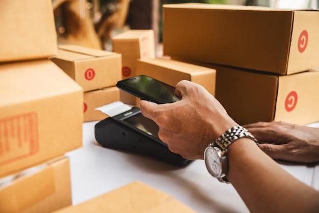 Main d'homme tenant la machine d'argent de la technologie de lecteur de carte de crédit nfc Photo Premium