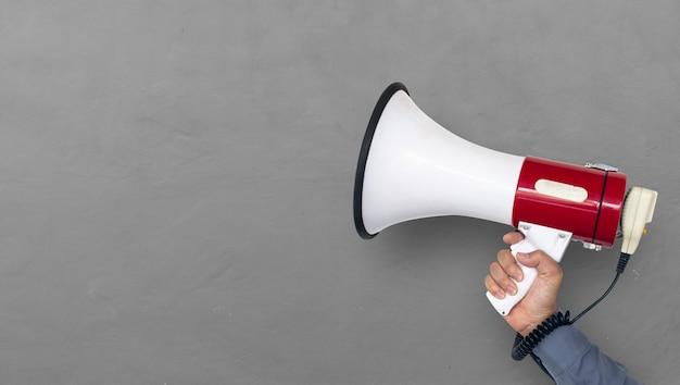 Main de l'homme tenant le mégaphone sur fond de mur de brique Photo Premium