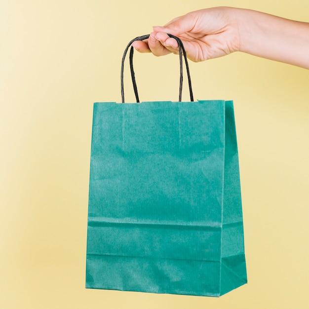 Main de l'homme tenant le sac de papier vert sur fond jaune Photo gratuit