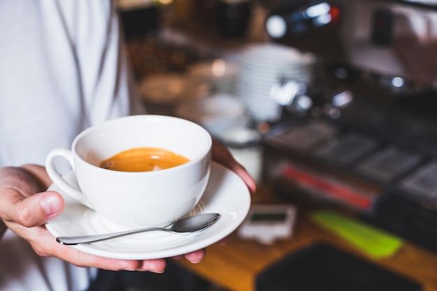 Main de l'homme tenant la tasse de café à la cafétéria Photo gratuit