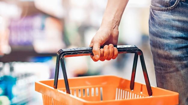 La Main De L'homme Tient Un Panier Vide Dans Le Supermarché. Concept D'épicerie Photo Premium