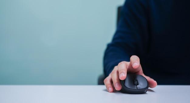 Main d'homme utilisant le curseur de la souris pour faire défiler une page web ou travailler sur ordinateur Photo Premium