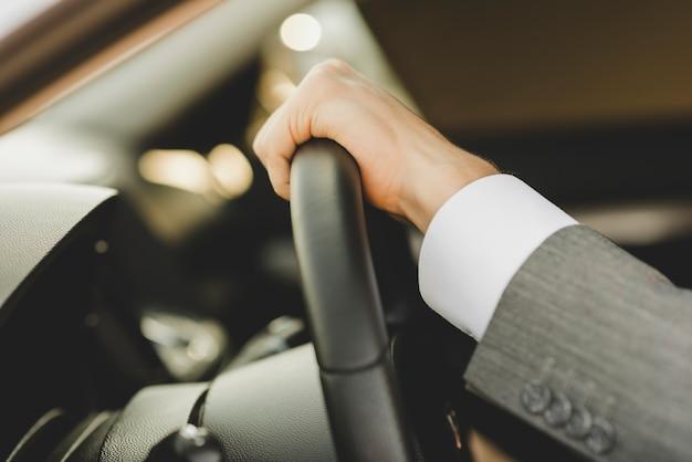 Main de l'homme sur le volant dans la voiture Photo gratuit