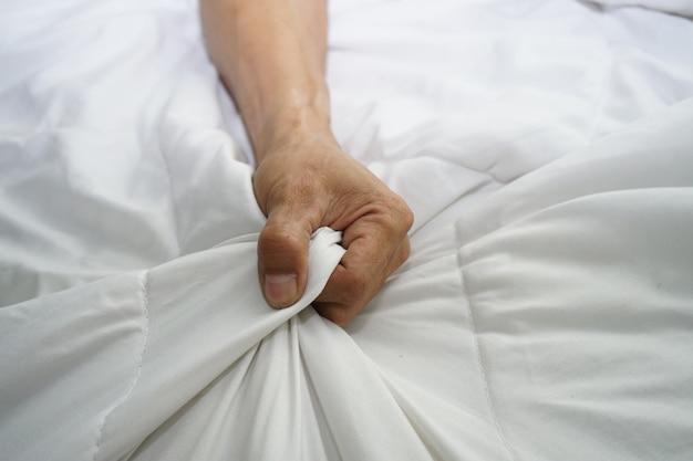 Main d'hommes tirant des draps blancs en extase, orgasme. Photo Premium
