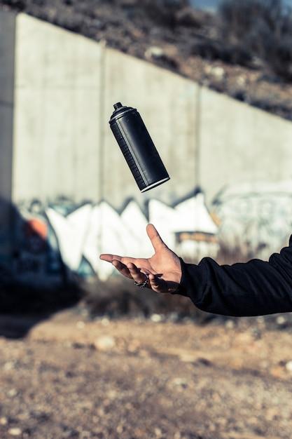 Main humaine attrapant la bombe aérosol noire Photo gratuit