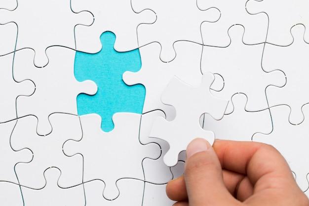 Main humaine insérant un puzzle blanc dans un espace vide Photo gratuit