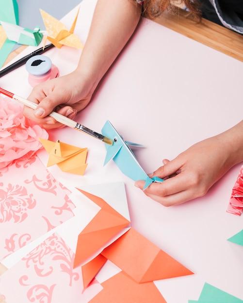 Main humaine, peinture de poisson origami à l'aide d'un pinceau Photo gratuit