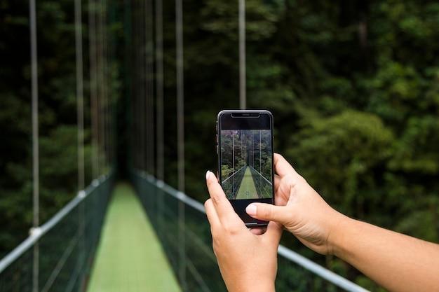 Main humaine prenant une photo d'un pont suspendu sur téléphone portable dans la forêt tropicale au costa rica Photo gratuit