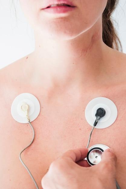 Main humaine avec stéthoscope vérifiant la respiration d'une femme Photo gratuit