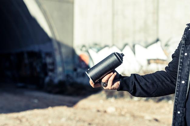 Main humaine tenant une bombe aérosol noire Photo gratuit