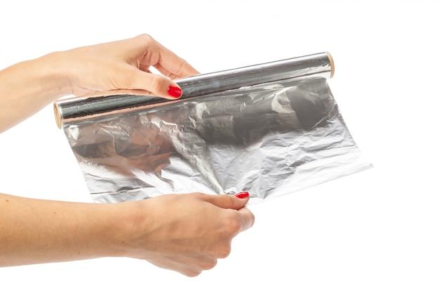 Main humaine tenant un rouleau de papier d'aluminium sur un blanc Photo Premium