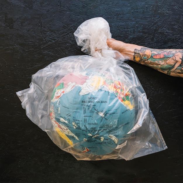 Main humaine tenant un sac en plastique avec globe Photo gratuit