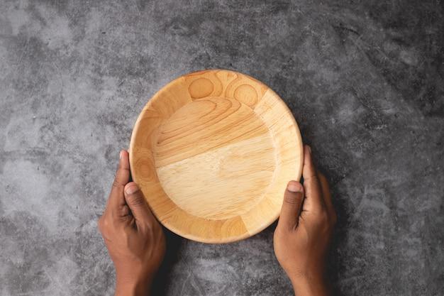 Main humaine tenir une plaque de bois vide sur fond de texture de mur de ciment. Photo Premium