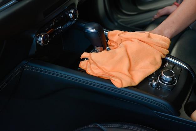 Main avec intérieur de voiture de nettoyage en tissu microfibre. Photo Premium