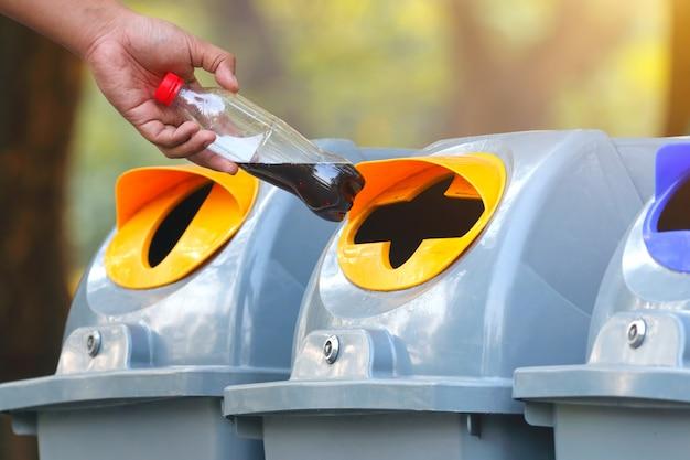 Main jetant une bouteille d'eau en plastique vide dans le bac de recyclage Photo Premium