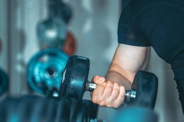 Main d'un jeune entraîneur musculaire beau bouchent avec un poids. Photo Premium