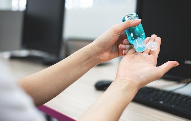 La Main D'une Jeune Femme Tenant Une Bouteille De Désinfectant Pour Les Mains Pour Empêcher L'hygiène D'un Coronavirus. Photo Premium