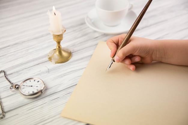 La Main De La Jeune Fille écrit Avec L'ancienne Poignée Sur Papier Photo Premium