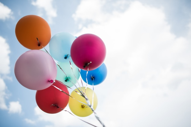 Main de jeune fille tenant des ballons colorés Photo gratuit