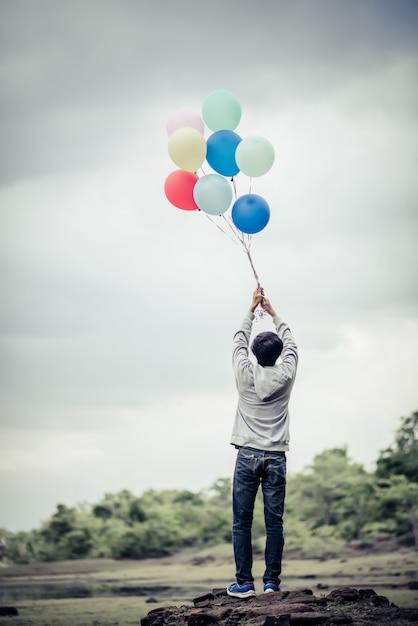 Main de jeune homme tenant des ballons colorés Photo gratuit