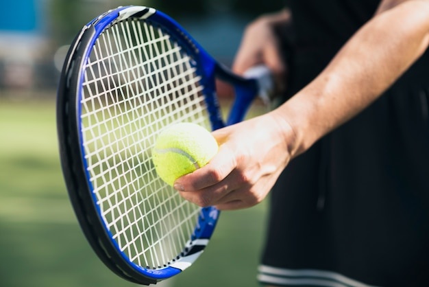 Main de joueur avec balle de tennis et raquette Photo gratuit