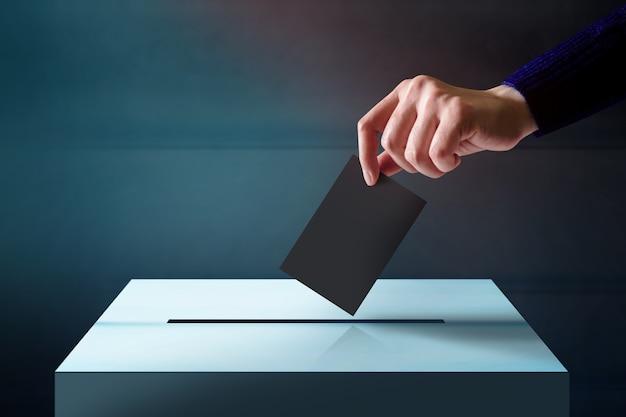 Main laissant tomber une carte de vote dans la boîte à vote Photo Premium