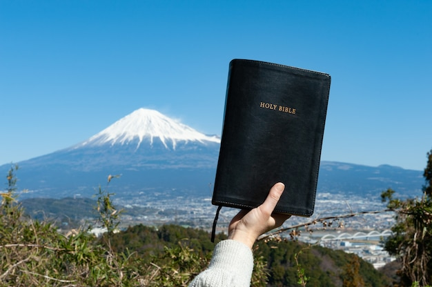 Main Levée Tenant La Sainte Bible Devant Le Mont Fuji Au Japon Photo Premium