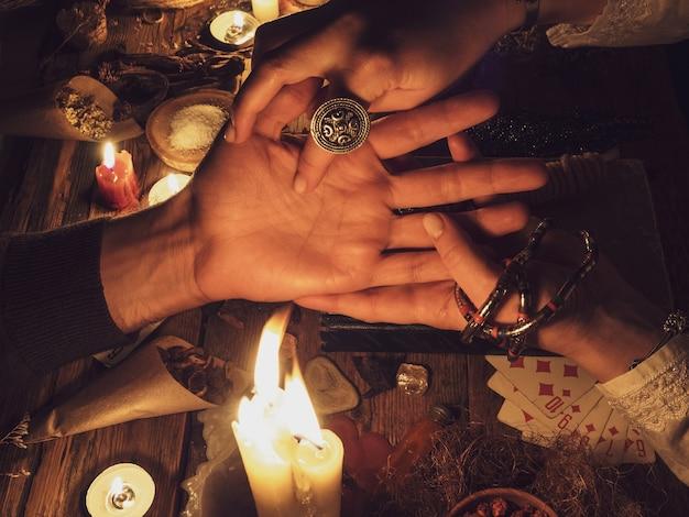 Main Lisant Dans Le Noir. Bougies Et Attributs De L'occulte Photo Premium