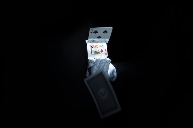 Main de magicien jetant des cartes à jouer sur fond noir Photo gratuit