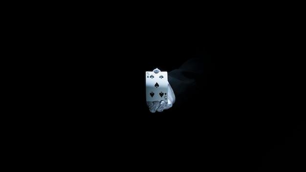 Main de magicien montrant la carte à jouer club sur fond noir Photo gratuit