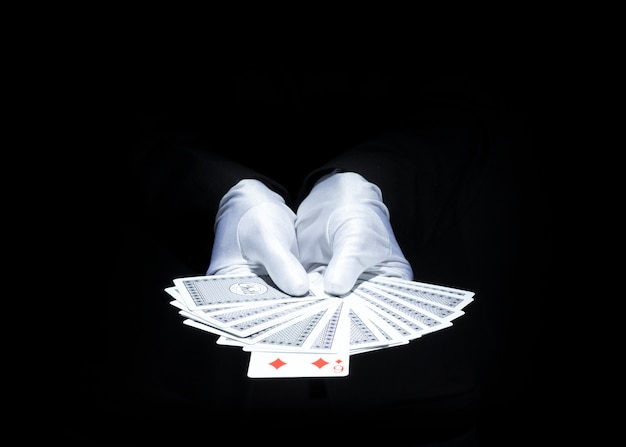 Main de magicien montrant le jeu de cartes avec un fond noir Photo gratuit