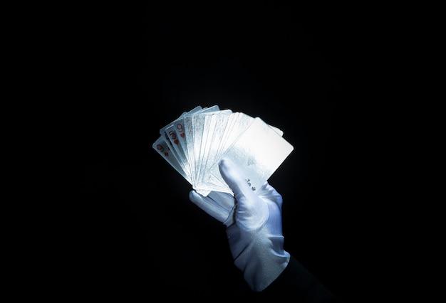 Main de magicien portant un gant blanc tenant des cartes à jouer attisées sur fond noir Photo gratuit