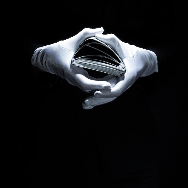 Main de magicien portant un gant blanc tenant la pile de cartes à jouer Photo gratuit