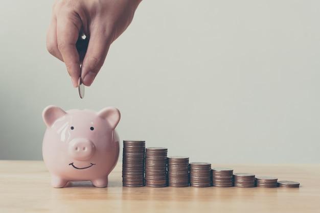 Main de mâle ou femelle mettant des pièces de monnaie dans la tirelire avec la pile d'argent Photo Premium