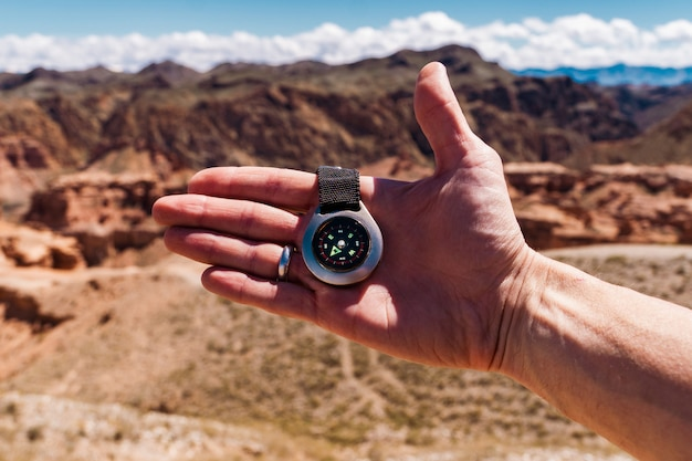 Main masculine avec boussole sur fond de montagnes en été, point de vue. Photo Premium