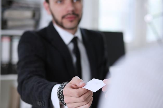 Une main masculine en costume donne une carte de visite vierge à une visiteuse agrandi. Photo Premium