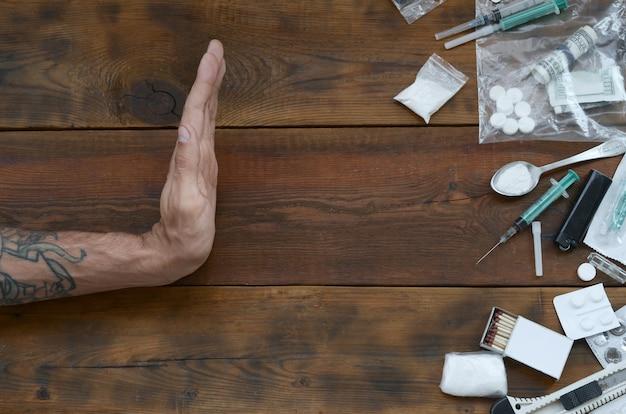 La Main Masculine Montre Le Signe Stop à Toutes Les Définitions De Stupéfiants. De Nombreuses Pilules De Drogue Et De Poudre Sur Une Table En Bois Photo Premium
