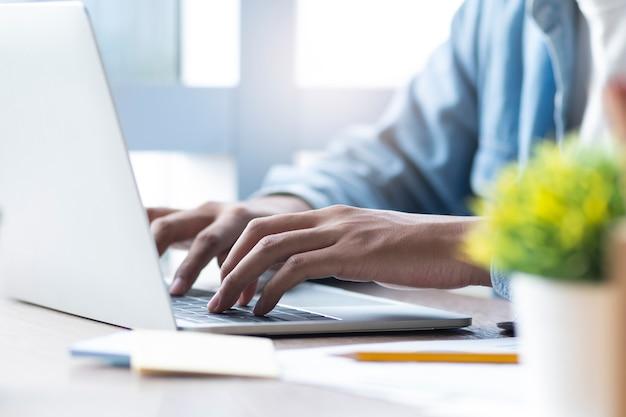Main masculine en tapant sur le clavier d'ordinateur portable. Photo Premium