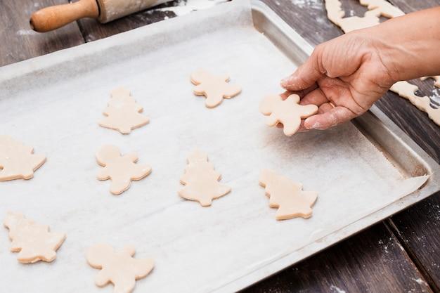 Main mettant des biscuits en forme de noël sur une plaque à pâtisserie Photo gratuit
