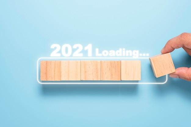 Main Mettant Le Bloc De Cubes En Bois Au Bloc Blanc Pour Le Compte à Rebours Et Le Chargement Jusqu'en 2021. Bonne Année Pour Démarrer Un Nouveau Projet Et Concept D'entreprise. Photo Premium
