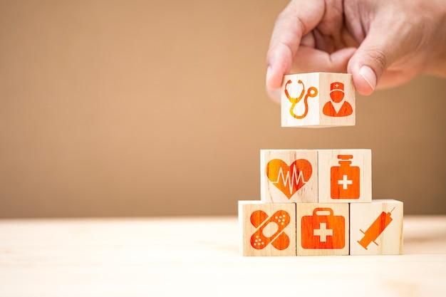 Main mettant des cubes en bois empilant des icône de médecine et d'hôpital sur la table. Photo Premium