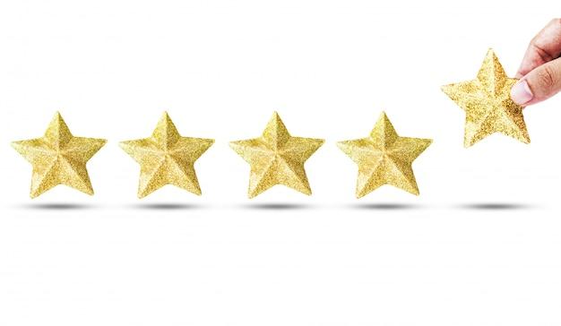 Main mettant les étoiles d'or de luxe Photo Premium