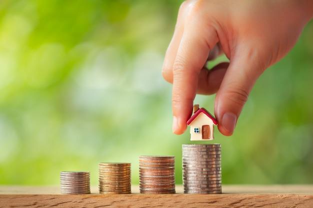 Main mettant le modèle de maison sur des piles de pièces Photo Premium