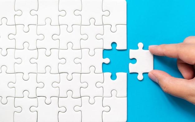 Main mettant le morceau de puzzle blanc sur fond bleu Photo Premium