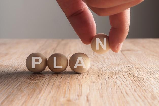 Main mettant sur le mot plan écrit dans une boule en bois Photo Premium