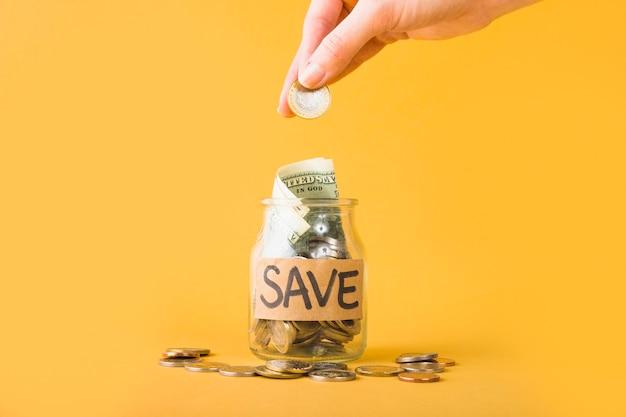 Main mettant la pièce dans un pot pour économiser Photo gratuit